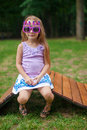 Cute little girl in purple happy birthday glasses sitting on wooden chair outdoor this image has attached release Royalty Free Stock Image