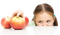 Cute little girl reaching apple table over white Stock Image