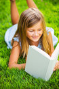 Cute little girl reading book outside on grass relaxing in backyard interesting Stock Photography