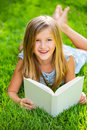 Cute little girl reading book outside on grass relaxing in backyard smiling Stock Photo