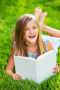 Cute little girl reading book outside on grass relaxing in backyard teeth Royalty Free Stock Photography