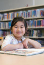 Cute Little Girl Reading Books at Library Stock Photography