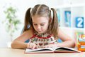 Cute little girl reading story from big book in the nursery room Royalty Free Stock Photography