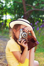 Cute little girl in retro outfit taking pictures with old film c Royalty Free Stock Photo