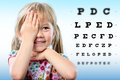 Cute little girl reviewing eyesight closing one eye with hand reading block letters on vision chart with focus point Stock Photos