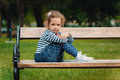 Cute little girl sitting on the bench in a park outdoors Royalty Free Stock Images