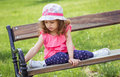 Cute little girl sitting on the bench in a park outdoors Stock Photos