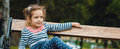 Cute little girl sitting on bench in park outside Royalty Free Stock Photo