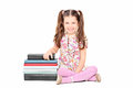 Cute little girl sitting next to a stack of books Stock Photo