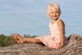 Cute little girl sitting on old tree Stock Images