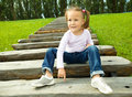 Cute little girl is sitting on stairs Royalty Free Stock Image