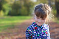 Cute little girl smiles and looks away in green park Royalty Free Stock Photo