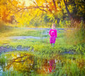 Cute little girl standing near a puddle Royalty Free Stock Photo