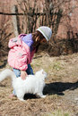 Cute little girl stroking white cat outdoors Stock Image