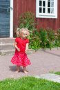 Cute little girl in summer dress blond with pigtails a red the garden front of a typical red wooden house sweden Stock Photo
