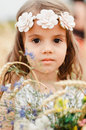 Cute little girl in the summer field of wheat. A child with a bouquet of wildflowers in his hands. Close up, Portrait Royalty Free Stock Photo