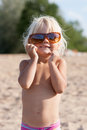 Cute little girl with sunglasses on the beach Stock Images