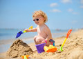 Cute little girl in sunglasses playing with sand at ocean beach Stock Images