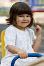 Cute little girl on swing in the playground white having fun at bright summer day Stock Photos