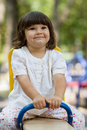 Cute little girl on swing in the playground white having fun at bright summer day Royalty Free Stock Photo