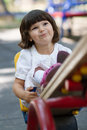 Cute little girl on swing in the playground white having fun at bright summer day Royalty Free Stock Images