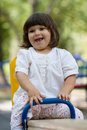 Cute little girl on swing in the playground white having fun at bright summer day Stock Photo