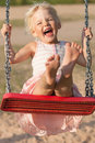 Cute little girl swinging laughs while Royalty Free Stock Photo