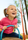 Cute little girl is swinging on see-saw Royalty Free Stock Photo