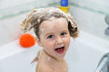Cute little girl taking a bath with foam childhood Stock Images