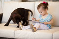 Cute little girl using a tablet pretty computer while her puppy keeps her company Royalty Free Stock Photo