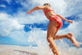 Cute little girl on vacation happy running and jumping at shallow water Royalty Free Stock Image
