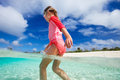 Cute little girl on vacation happy running and jumping at shallow water Royalty Free Stock Photo
