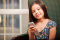 Cute little girl watching tv portrait of a pretty hispanic holding a remote and smiling Stock Photography