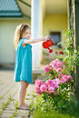 Cute little girl watering flowers in the garden Royalty Free Stock Image