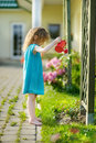 Cute little girl watering flowers in the garden Royalty Free Stock Photography