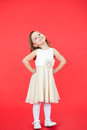 Cute little girl in white dress posing on red background Royalty Free Stock Photo