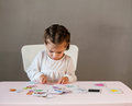Cute little girl in white shirt playing puzzle. Royalty Free Stock Photo