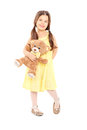 Cute little girl in yellow dress holding a teddy bear Stock Images