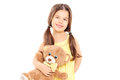Cute little girl in yellow dress holding a teddy bear isolated on white background Stock Photos