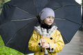 Cute little girl in a yellow raincoat with umbrella Royalty Free Stock Photo