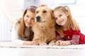 Cute little girls with pet dog smiling lying prone on floor huddling up against golden retriever Royalty Free Stock Images