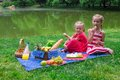 Cute little girls picnicing in the park at sunny two on picnic Stock Images