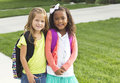 Cute little girls walking to school together two with backpacks ready walk Royalty Free Stock Photography