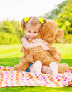 Cute little happy girl hugging big brown teddy bear and sitting down on green grass meadow spring season Stock Photo