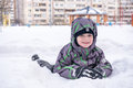 Cute little kid boy in colorful winter clothes laying down on . Active outdoors leisure with children in . Happy child. Royalty Free Stock Photo