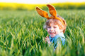 Cute little kid boy with easter bunny ears in green grass on holiday celebrating traditional european feast and making egg Royalty Free Stock Photography