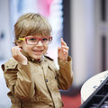 Cute little kid boy at optician store during choosing his new gl Royalty Free Stock Photo