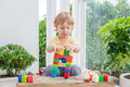 Cute little kid boy with playing with lots of colorful plastic blocks indoor. Active child having fun with building and creating o