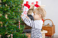 Cute little kid decorating Christmas tree, indoor Royalty Free Stock Photo