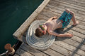 Cute little kid sunbathing lying on rope and wooden pier Royalty Free Stock Photo